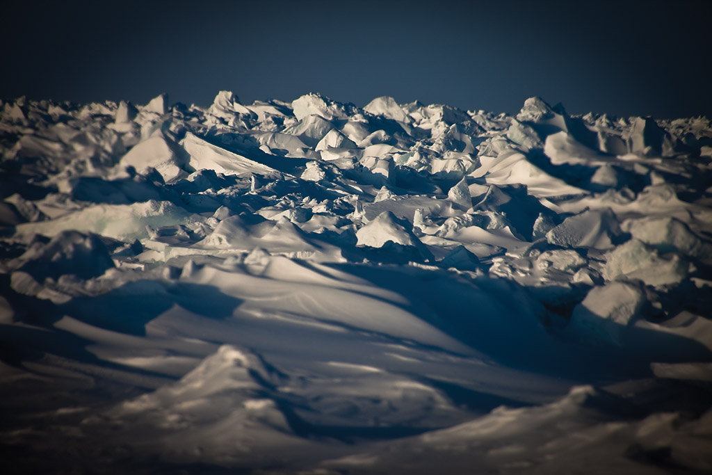 "The terrain is rarely flat due to the constant motion of the sea ice, fragmenting and accumulating into pressure ridges or endless ""rubble fields""."